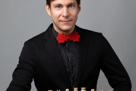 ROCO Guest Composer Maxime Goulet posing with a chess board ahead of the premiere of Checkmate